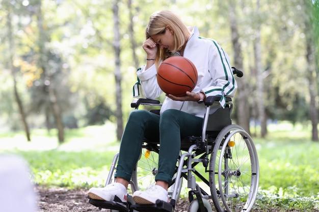 Niepełnosprawna kobieta na wózku inwalidzkim trzymająca piłkę do koszykówki i płacząca urazy sportowe powodujące