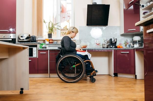 Niepełnosprawna kobieta robi sałatkę w kuchni
