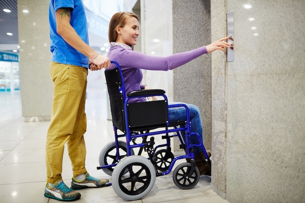 Niepełnosprawna kobieta używa windę