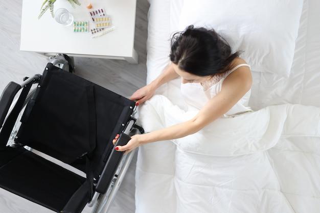 Niepełnosprawna kobieta wstaje z łóżka i trzyma wózek inwalidzki