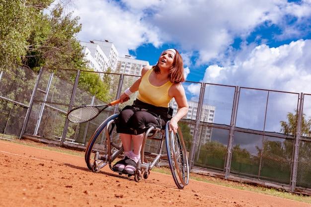 Niepełnosprawna młoda kobieta bawić się tenisa na korcie tenisowym na wózku inwalidzkim.