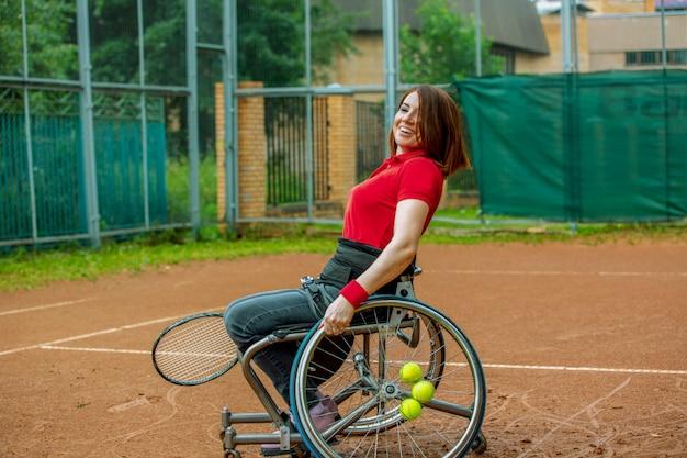 Niepełnosprawna młoda kobieta bawić się tenisa na tenisowym korcie na wózku inwalidzkim