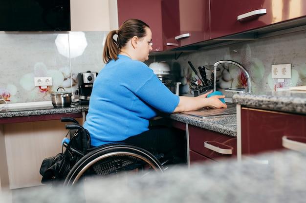 Niepełnosprawna młoda kobieta na wózku inwalidzkim zmywa naczynia w specjalnie wyposażonej kuchni