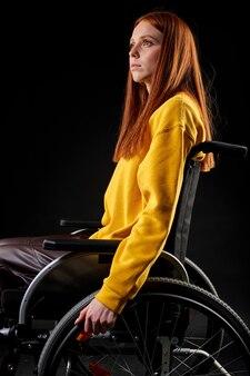Niepełnosprawna ruda kobieta siedzi patrząc w górę, młoda kobieta w swobodnym stroju marzy, ma myśli. pojedyncze czarne tło. widok z boku