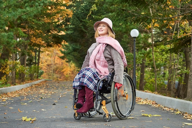 Niepełnosprawna, sparaliżowana uśmiechnięta kobieta na wózku inwalidzkim porusza się w jesiennym parku