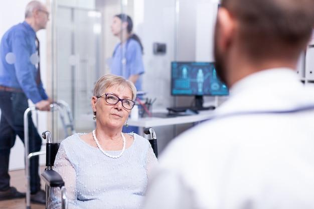 Niepełnosprawna stara kobieta siedząca na wózku inwalidzkim podczas badania lekarskiego z diagnozą lekarską i słuchającą