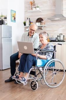 Niepełnosprawna starsza kobieta na wózku inwalidzkim i jej mąż szukający na laptopie, surfujący w mediach społecznościowych, siedzący rano w kuchni. sparaliżowana niepełnosprawna osoba starsza mająca konferencję online.