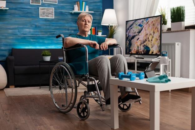 Niepełnosprawna starsza kobieta na wózku inwalidzkim, patrząca na gimnastyczne wideo online na tablecie tablet