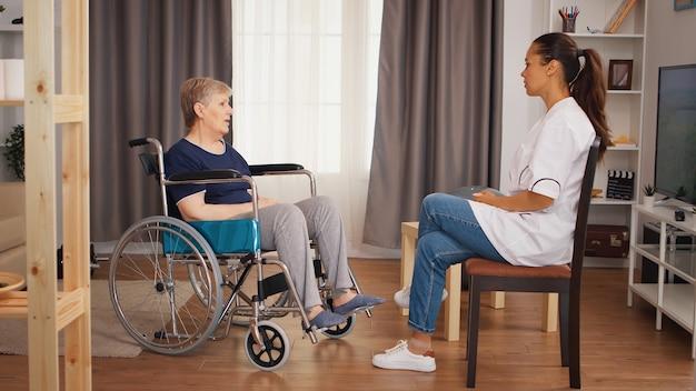 Niepełnosprawna starsza kobieta na wózku inwalidzkim rozmawia z lekarzem. dom spokojnej starości, opieka zdrowotna, pomoc zdrowotna, pomoc społeczna, lekarz i opieka domowa