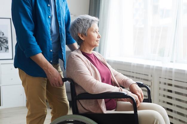 Niepełnosprawna starsza kobieta siedząca na wózku inwalidzkim i patrząc przez okno z opiekunem stojącym w pobliżu