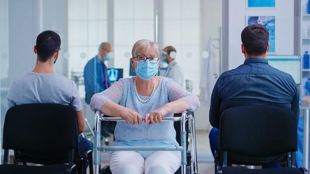 Niepełnosprawna starsza kobieta z ramą spacerową w poczekalni szpitala patrząc na kamery. dojrzała kobieta nosi maskę przeciwko koronawirusowi. pielęgniarka w sali egzaminacyjnej.