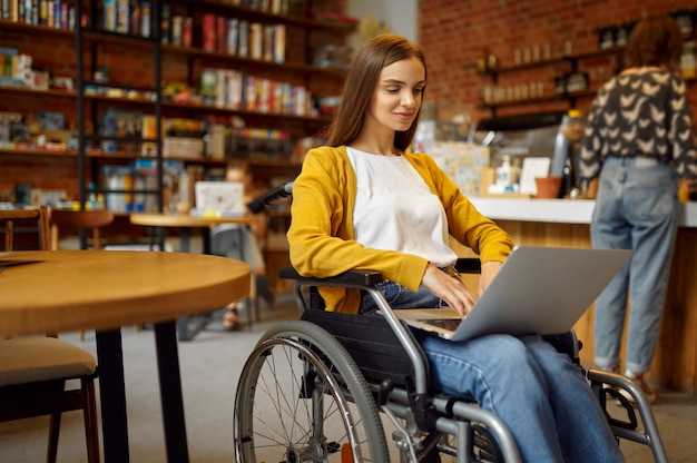 Niepełnosprawna studentka na wózku inwalidzkim działa na laptopie, niepełnosprawności, półce na książki i wnętrzu biblioteki uniwersyteckiej na tle. niepełnosprawna młoda kobieta studiująca na studiach, sparaliżowani ludzie zdobywają wiedzę