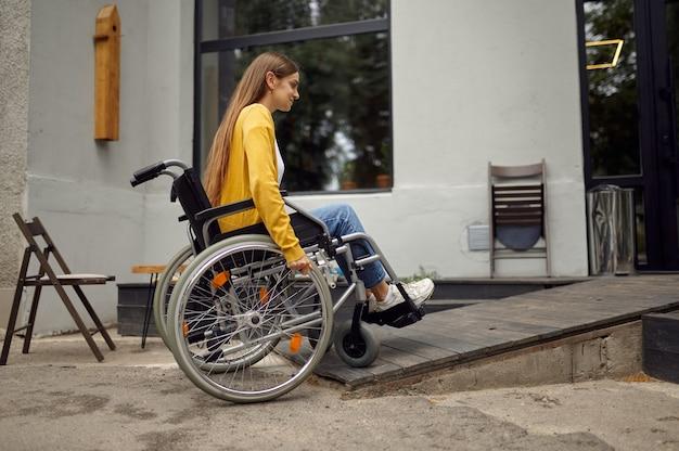 Niepełnosprawna studentka na wózku inwalidzkim na rampie w kawiarni uniwersyteckiej, niepełnosprawność. niepełnosprawna młoda kobieta studiująca na studiach, sparaliżowani ludzie zdobywają wiedzę