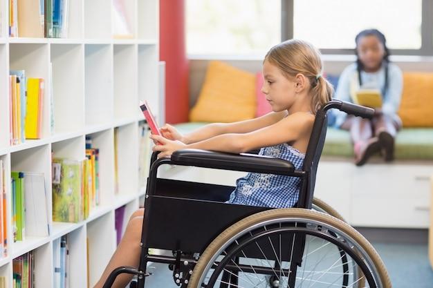 Niepełnosprawna uczennica wybiera książkę z półki w bibliotece