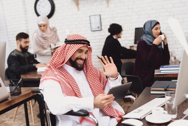 Niepełnosprawni arabscy wideo dzwoni przerwa na kawę przy pracą.