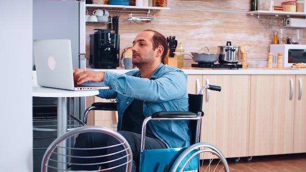 Niepełnosprawni biznesmen na wózku inwalidzkim za pomocą laptopa w kuchni. biznesmen z paraliżem, niepełnosprawnością, niepełnosprawnością, niepełnosprawnością, trudnościami w pracy po wypadku, podczas wideokonferencji przez internet