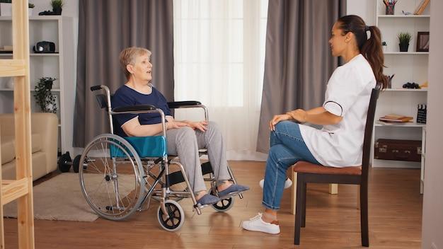 Niepełnosprawni starsza kobieta na wózku inwalidzkim rozmawia z pielęgniarką. dom spokojnej starości, opieka zdrowotna, pomoc zdrowotna, pomoc społeczna, lekarz i opieka domowa