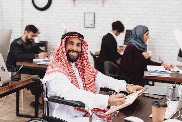 Niepełnosprawny arabski pracownik biurowy w keffiyeh ono uśmiecha się