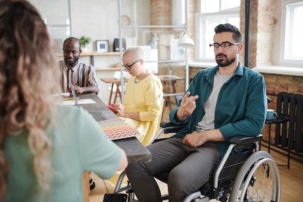 Niepełnosprawny biznesmen siedzi na wózku inwalidzkim i gestykuluje, pracuje z kolegami na spotkaniu biznesowym w biurze