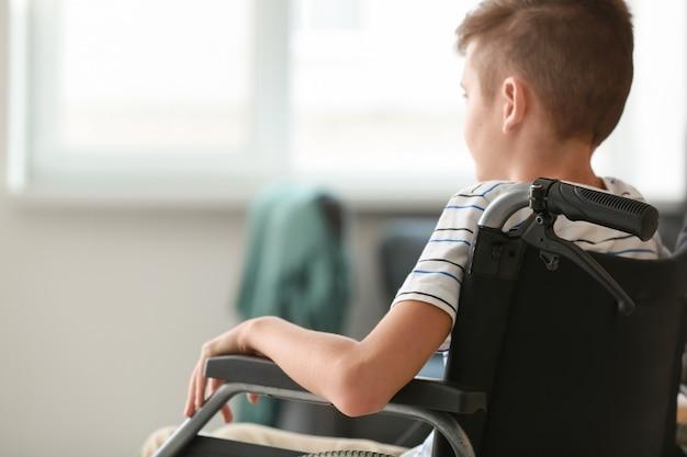 Niepełnosprawny chłopiec na wózku inwalidzkim w domu