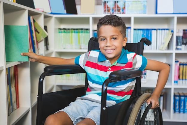 Niepełnosprawny chłopiec wybiera książkę z półka na książki w bibliotece