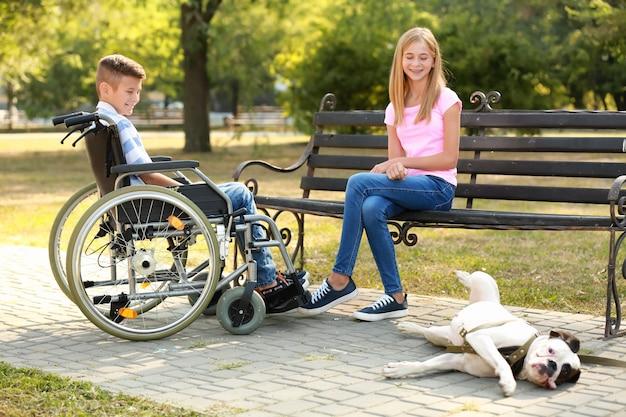 Niepełnosprawny chłopiec z siostrą i psem odpoczywają w parku
