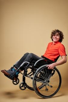 Niepełnosprawny człowiek bawić się siedząc na wózku inwalidzkim, uśmiechając się do kamery, w akcji. na białym tle beżowym tle