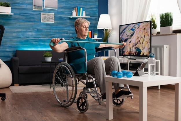 Niepełnosprawny emeryt na wózku inwalidzkim, pracujący z taśmą elastyczną, trenujący mięśnie ciała, regenerujące się po wypadku inwalidzkim, patrząc na wideo z aerobiku na tablecie. emeryt robi ćwiczenia ramion w służbie zdrowia