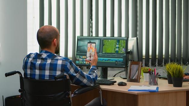 Niepełnosprawny filmowiec na wózku inwalidzkim rozmawiający przez kamerę internetową z cowerkerami podczas montażu projektu wideo tworzącego treści w nowoczesnym biurze firmy. twórca blogera pracującego w studiu fotograficznym.