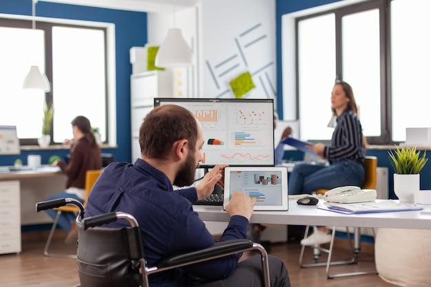 Niepełnosprawny inwalida pracownik siedzący unieruchomiony na wózku inwalidzkim pracujący przy notatniku i komputerze jednocześnie analizujący wykresy finansowe, komputer pokazujący przetwarzanie danych dla projektu dotyczącego gospodarki
