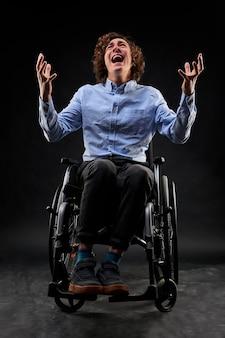 Niepełnosprawny mężczyzna krzyczy rozpacz siedzi na wózku inwalidzkim na białym tle na czarnym tle. portret niepełnosprawnego mężczyzny podnoszącego ręce i krzyczącego na cały głos