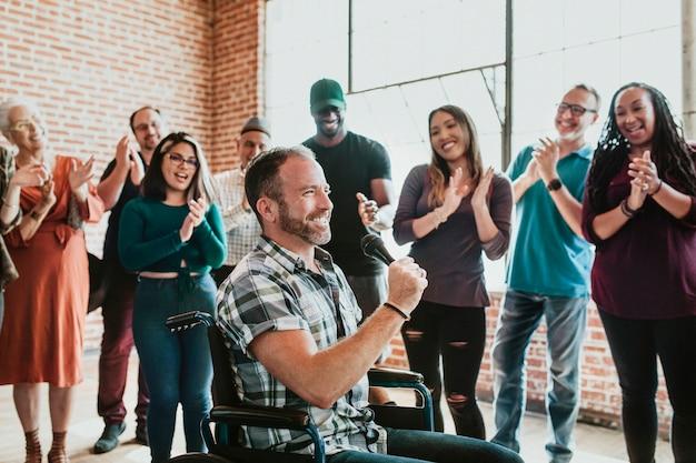 Niepełnosprawny mężczyzna mówiący przez mikrofon w warsztacie