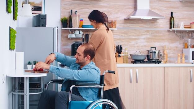 Niepełnosprawny mężczyzna na wózku inwalidzkim do krojenia papryki w kuchni pomaga żonie do gotowania pysznego posiłku. facet z paraliżem niepełnosprawność niepełnosprawna niepełnosprawność niepełnosprawność pomoc w kuchni