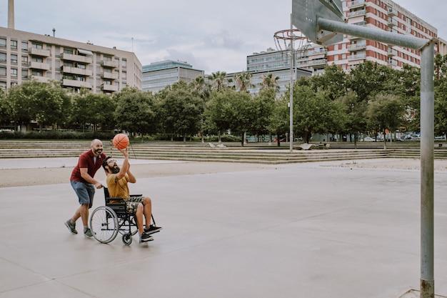 Niepełnosprawny mężczyzna na wózku inwalidzkim gra z przyjacielem w koszyku