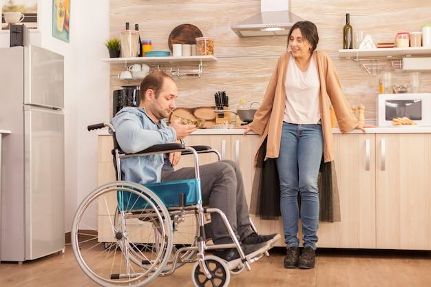 Niepełnosprawny mężczyzna na wózku inwalidzkim, patrząc na sałatkę wykonaną przez żonę w kuchni. niepełnosprawny, sparaliżowany, niepełnosprawny mężczyzna z niepełnosprawnością chodu, integrujący się po wypadku.