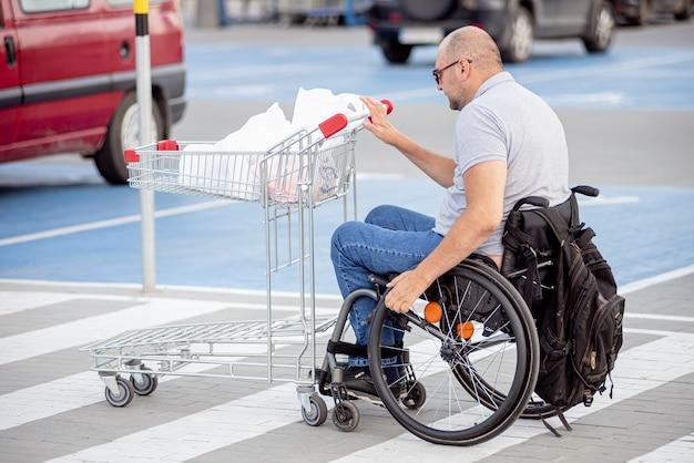 Niepełnosprawny mężczyzna na wózku inwalidzkim pchający wózek przed sobą na parkingu w supermarkecie