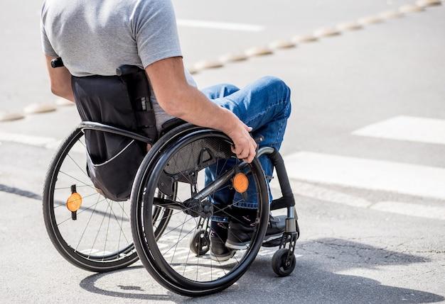 Niepełnosprawny mężczyzna na wózku inwalidzkim przygotowuje się do przejścia przez jezdnię na przejściu dla pieszych.