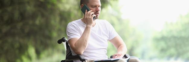 Niepełnosprawny mężczyzna na wózku inwalidzkim rozmawia przez telefon komórkowy w parku