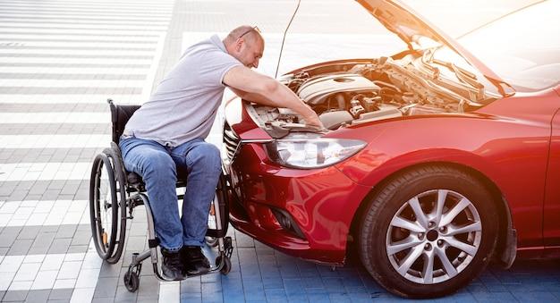 Niepełnosprawny mężczyzna na wózku inwalidzkim, sprawdza silnik swojego samochodu na parkingu