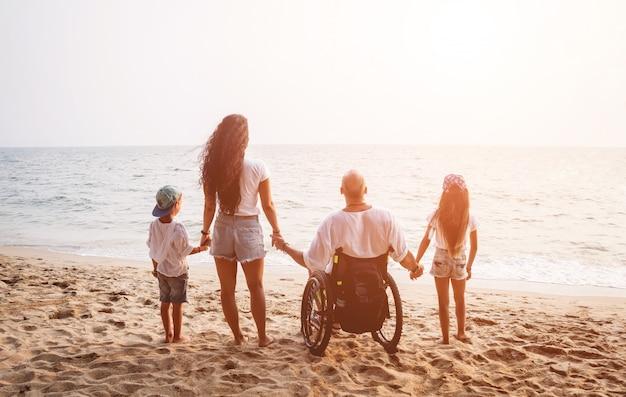 Niepełnosprawny mężczyzna na wózku inwalidzkim z rodziną na plaży.