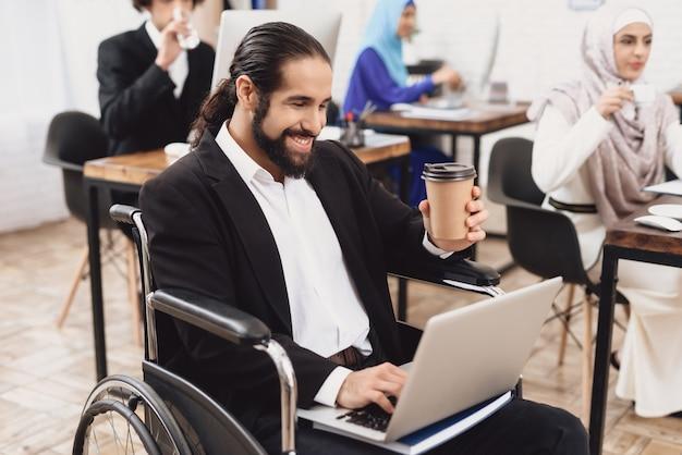 Niepełnosprawny mężczyzna pije kawę szczęśliwy pracownik biurowy.