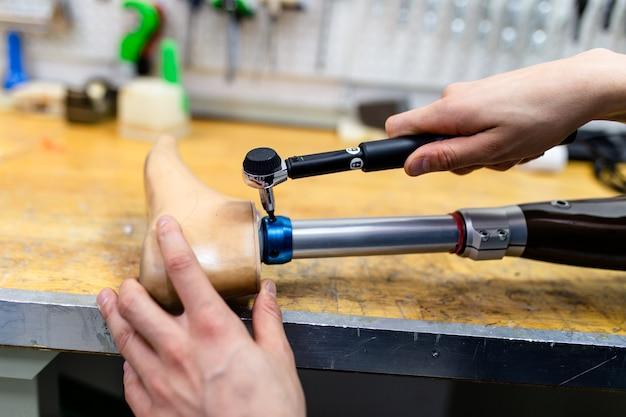 Niepełnosprawny mężczyzna pracujący w sklepie po amputacji do produkcji części protetycznych kończyn.