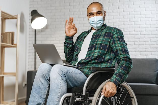 Niepełnosprawny mężczyzna siedzący na wózku inwalidzkim i korzystający z laptopa z założoną maską na twarz