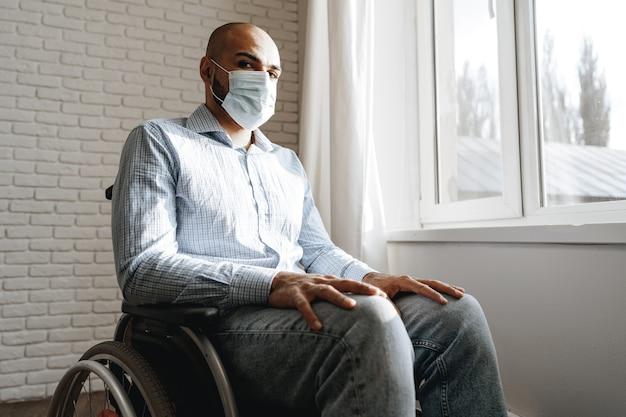 Niepełnosprawny mężczyzna siedzący na wózku inwalidzkim i noszący maskę na twarz