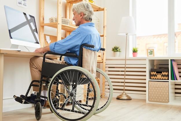 Niepełnosprawny mężczyzna używa komputer w domu