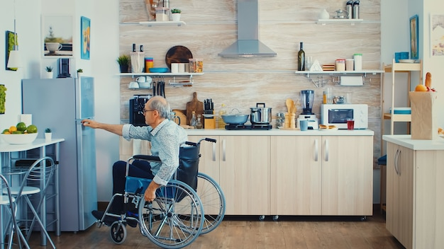 Niepełnosprawny mężczyzna w wózku inwalidzkim otwierając lodówkę i pomagając żonie przygotowywać śniadanie w kuchni. starsza kobieta pomaga nieważnemu mężowi. życie z osobą niepełnosprawną z niepełnosprawnością ruchową