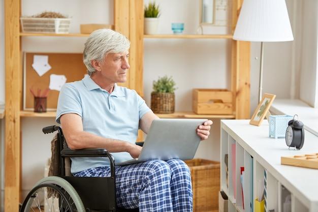 Niepełnosprawny mężczyzna z laptopem w domu