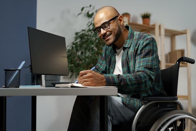 Niepełnosprawny młody afroamerykanin na wózku inwalidzkim przy użyciu komputera siedząc przy stole roboczym his