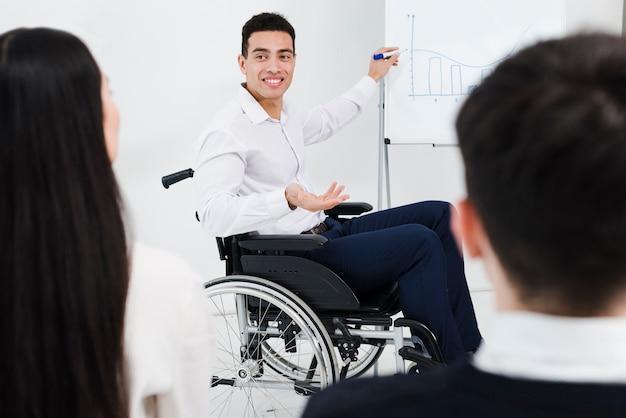 Niepełnosprawny młody biznesmen siedzi na wózku inwalidzkim, dając prezentacji do swojego kolegi w biurze