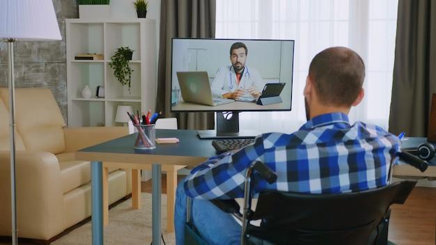 Niepełnosprawny młody człowiek na wózku inwalidzkim podczas rozmowy wideo z lekarzem.